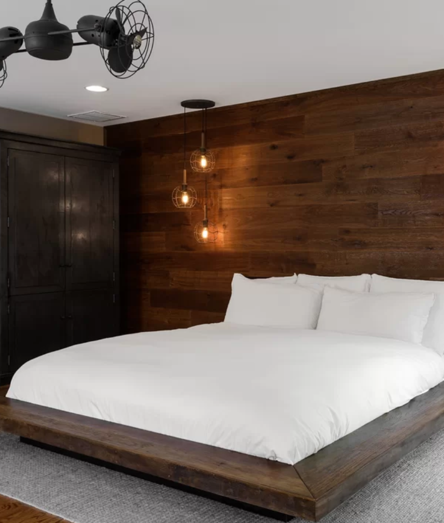 Rustic bedroom with hardwood walls and floors along with white regular ceiling and stylish pendant lights.