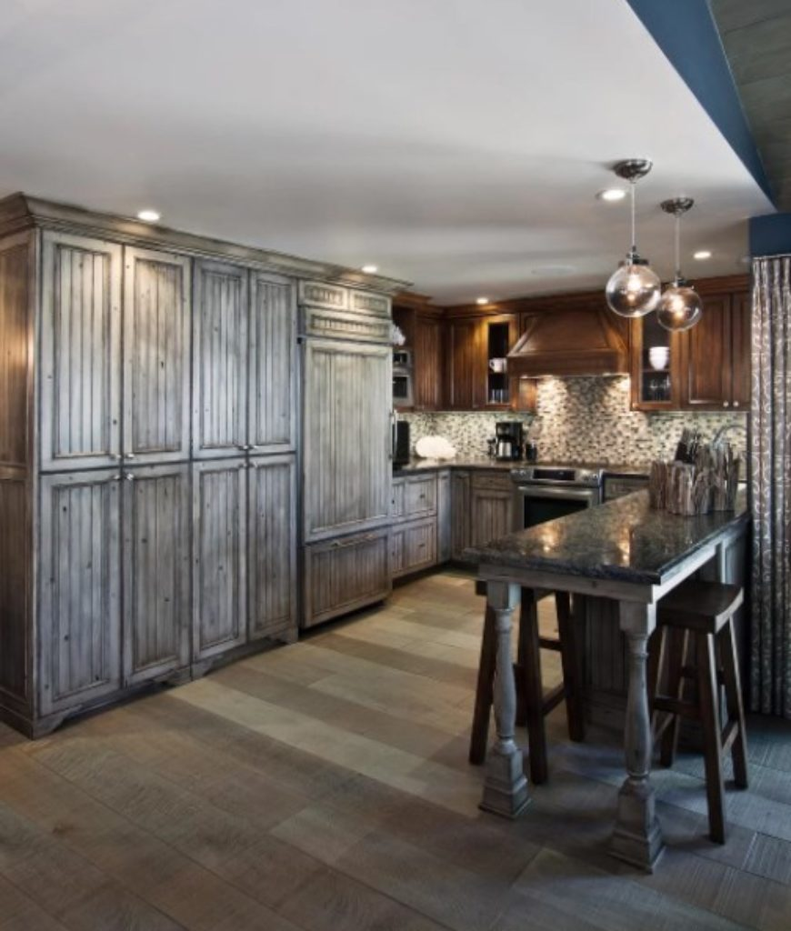 Rustic kitchen with large reach-in cabinets and marble breakfast island.