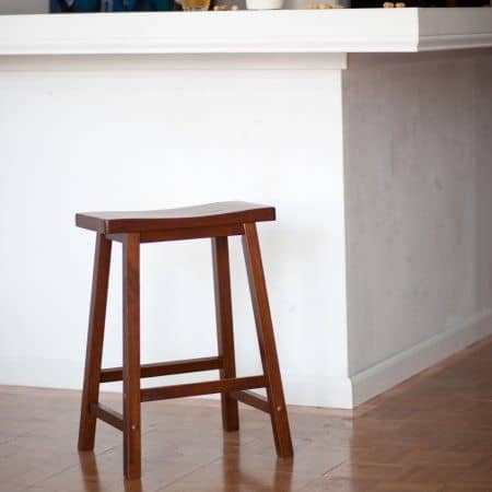 Saddle seat counter stool with warm walnut stain finish and durable frame.