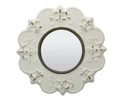 A small mirror in a ceramic ivory frame creating the perfect Parisian style.