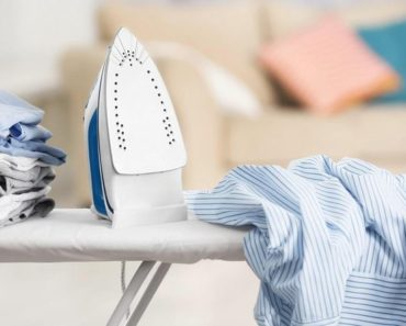 Small iron on a white ironing board.