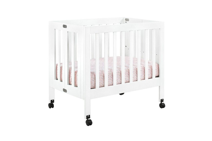 Portable white mini crib with stationary front and back rail and two position mattress height adjustment.