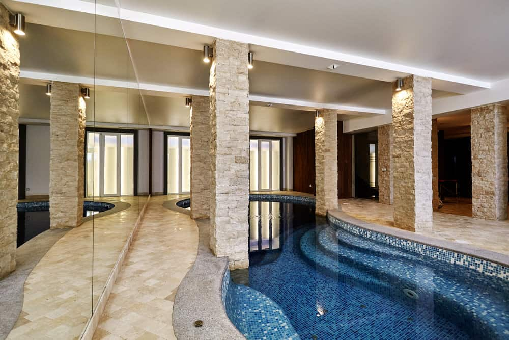 Luxurious curved pools framed with stone brick columns that complement with the tiled flooring for a cohesive look.
