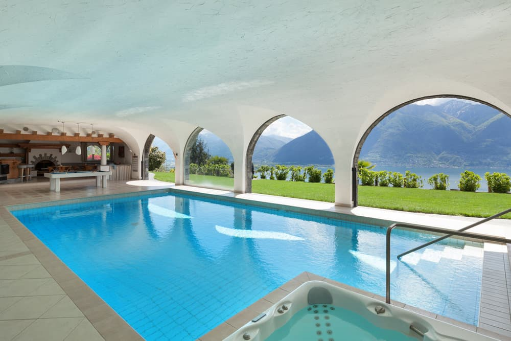 An L-shaped swimming pool fitted with a jacuzzi and lined with open archways overlooking a breathtaking mountain view.