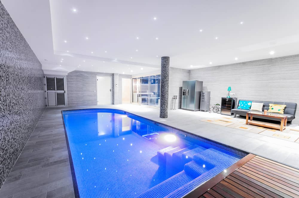 Deluxe swimming pool with a black mosaic accent wall that matches with the column. It offers a fridge and gray tufted sofa topped with fluffy pillows and paired with a wooden coffee table.