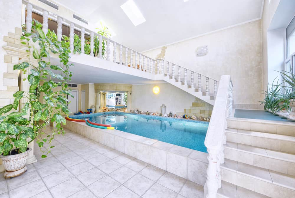 A classic pool underneath the staircase framed with ornate spindles and clad in white stone tiles that match with the flooring.