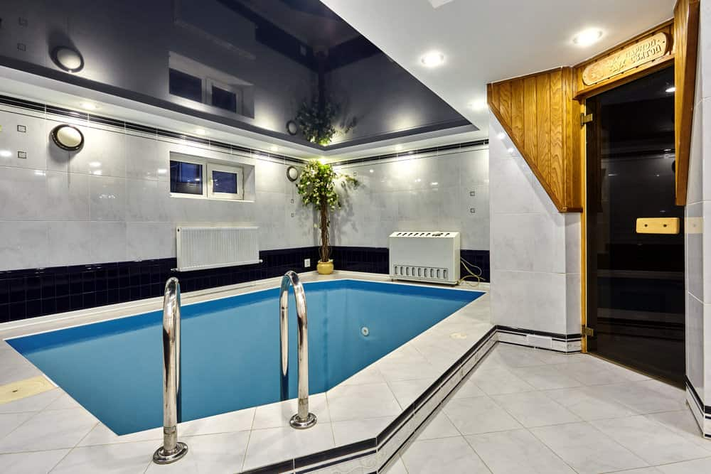 A luxury swimming pool features a dark mirrored ceiling and concrete tiled deck with black accent lining complementing with the glossy wall.