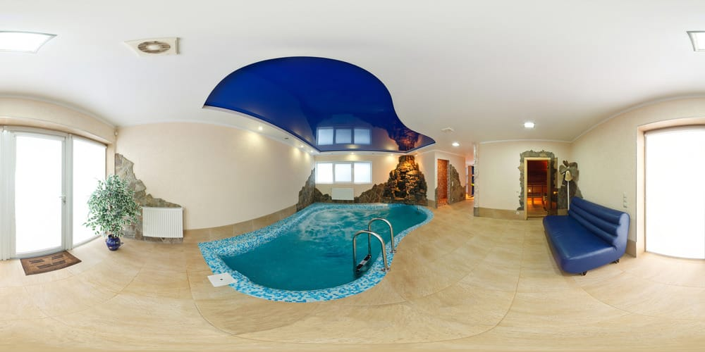 Gorgeous house boasts an indoor pool with mosaic surround tiles and a ceiling accented with the shape of the pool.
