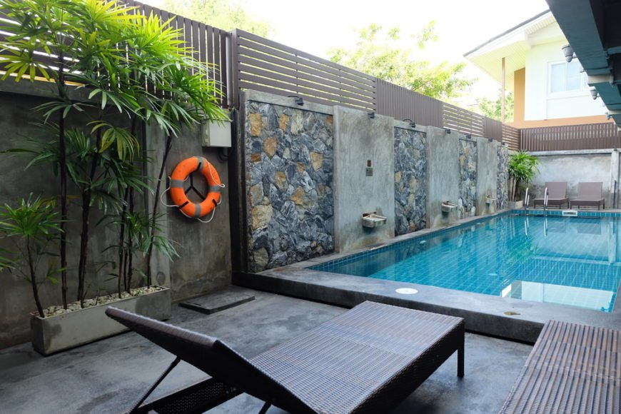 Tranquil swimming pool accented with lovely stone wall panels along with planters that create a refreshing ambiance to this area.