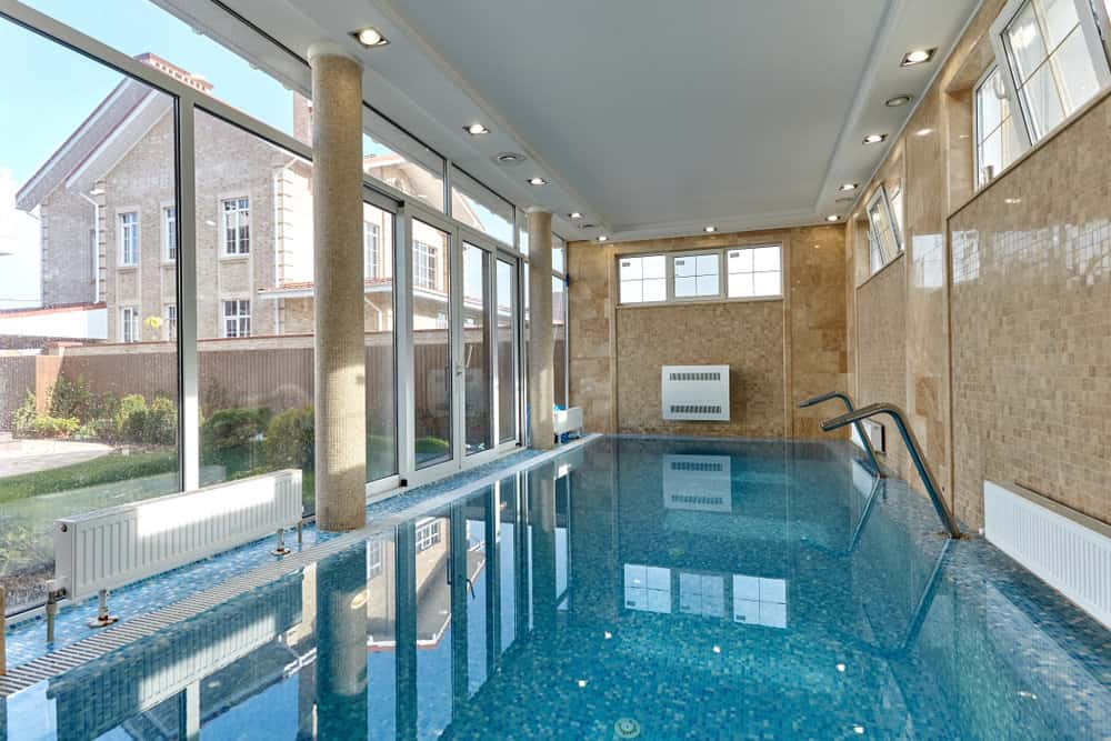 A gorgeous indoor pool showcases tray ceiling fixed with recessed lights and full height glazing allowing plenty of natural light in.