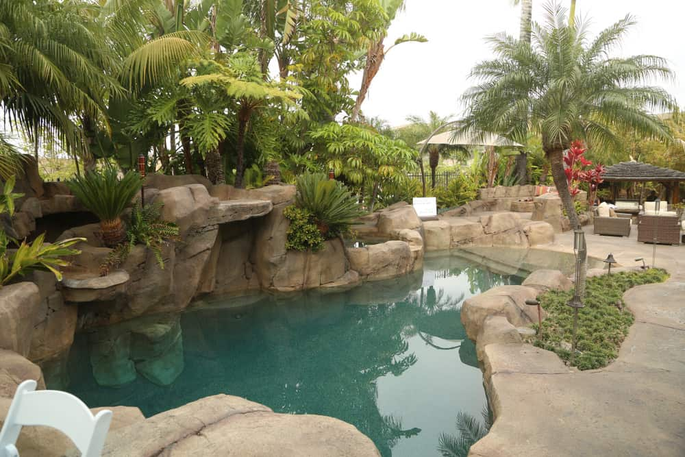 A freeform swimming pool surrounded by big rocks and greenery. It has rattan chairs on the side topped with gray cushions and pillows.