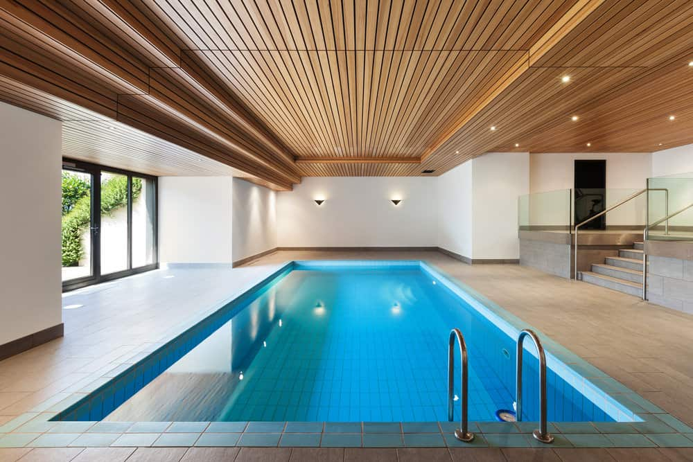 A concrete staircase framed with glass railings leads to this swimming pool illuminated by wall sconces and recessed lights fixed to the wood plank ceiling.