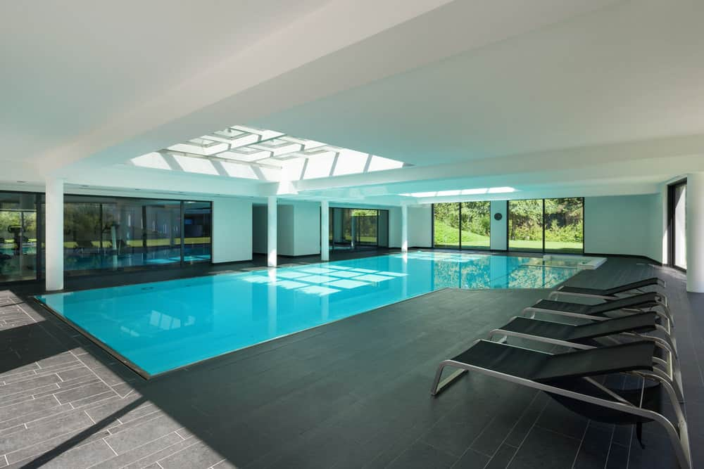 An indoor pool with black lounge chairs over the black tiled deck and a pair of paneled skylights fitted to the white ceiling.