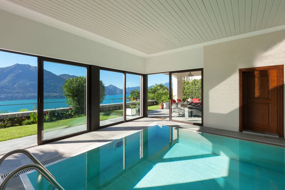 An indoor pool boasting a shiplap ceiling and panoramic windows overlooking a spectacular mountain view.