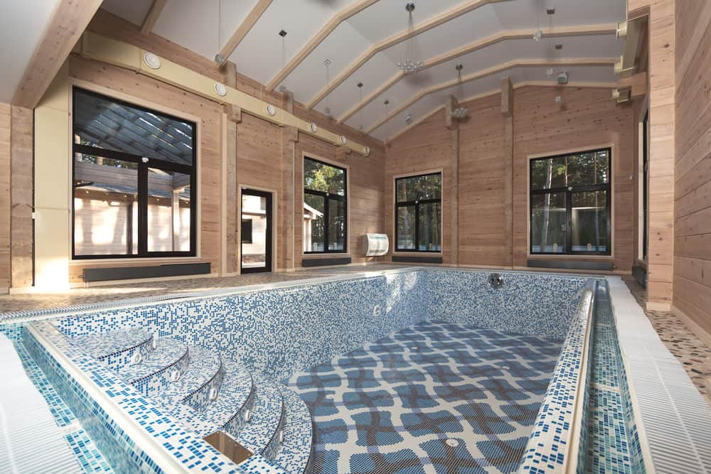 An all-wood house with glazed windows and a stunning swimming pool where you can clearly see the blue mosaic tiles and its striking patterned design.