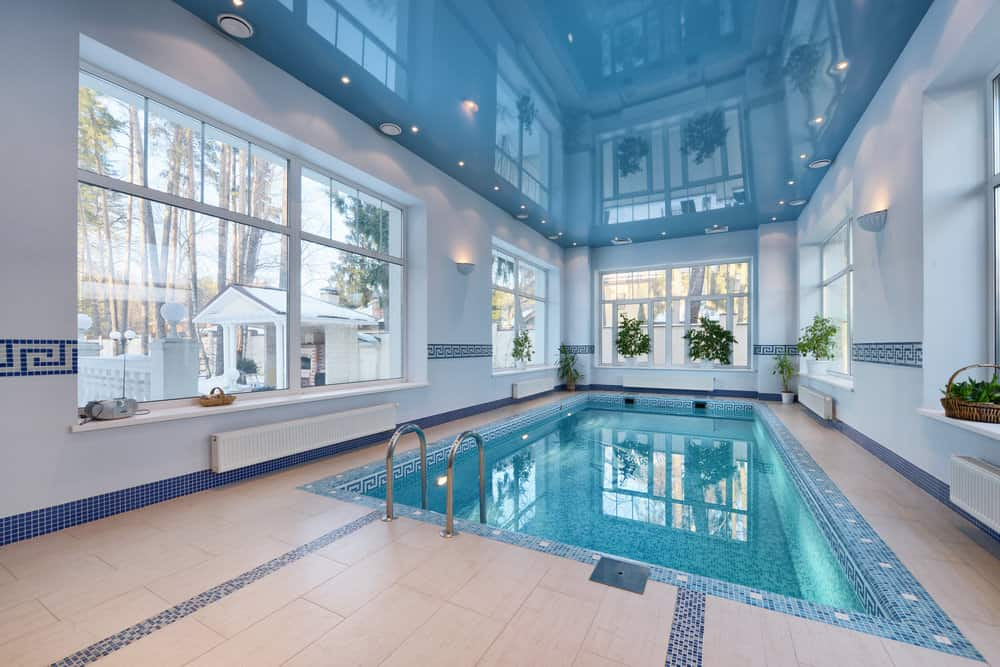 A fresh swimming pool surrounded with paneled glass windows bringing plenty of natural light in. It has an aqua frosted mirror ceiling fitted with flush mount and recessed lighting.