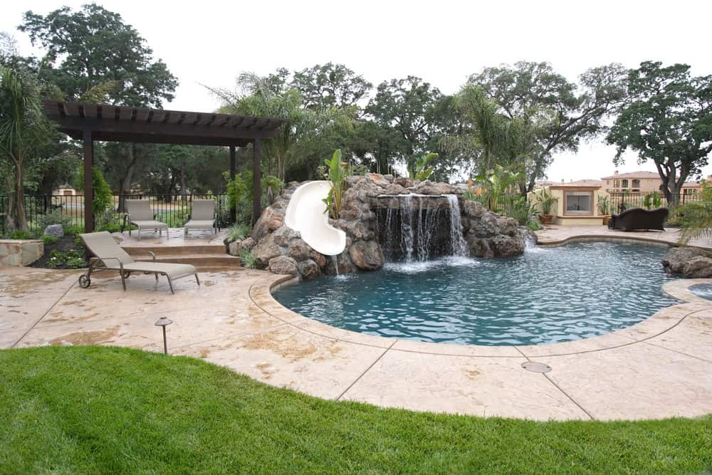 A kidney pool accented with a waterfall and slide that's fixed to the boulder next to the dark wood pergola with gray lounge chairs.