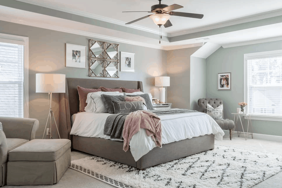 Traditional light gray bedroom with carpet flooring and soft rug together with tray ceiling and flushmount lighting.