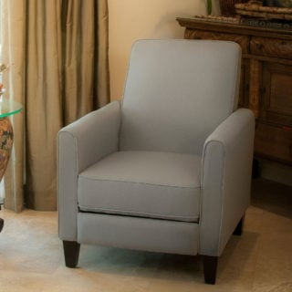 Recliner club chair with foot extension and reclining back features and solid fabric upholstery.