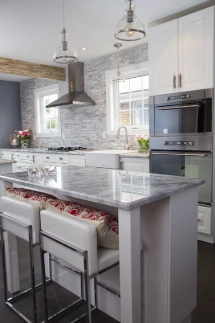 White contemporary kitchen with 1-light inverted pendant lighting with marble breakfast island and hardwood flooring.