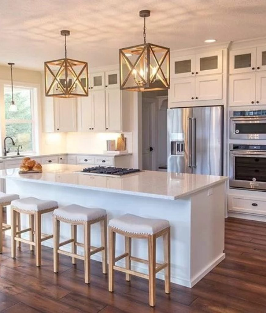 White cottage kitchen with 4-light chandelier, marble breakfast island, bar stools, stainless steel appliances and hardwood flooring.