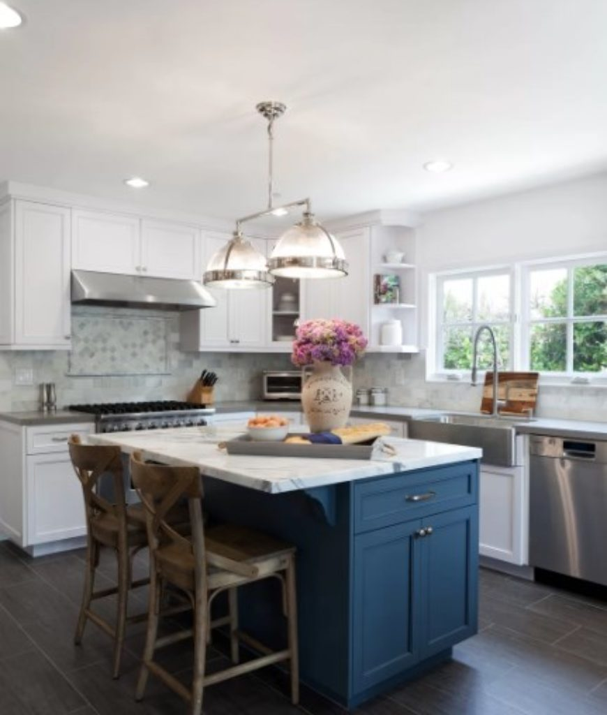 White country kitchen with blue breakfast island and classy pendant lighting.