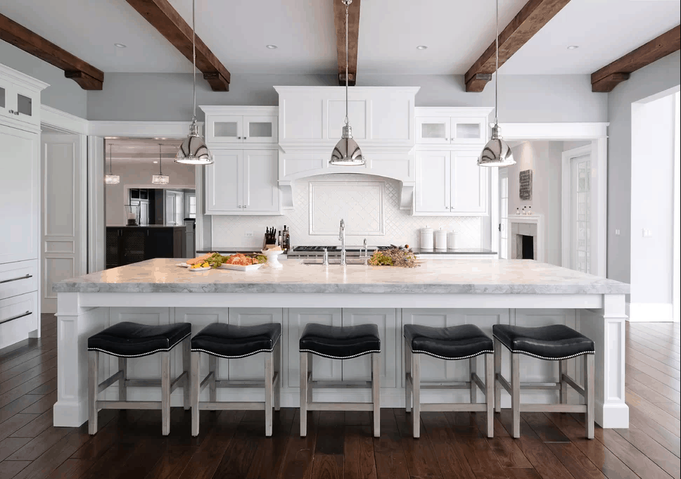 Gorgeous kitchen with dark wood plank flooring and white ceiling lined with wood beams. It has gray breakfast island with black bar stools lighted by chrome pendants.