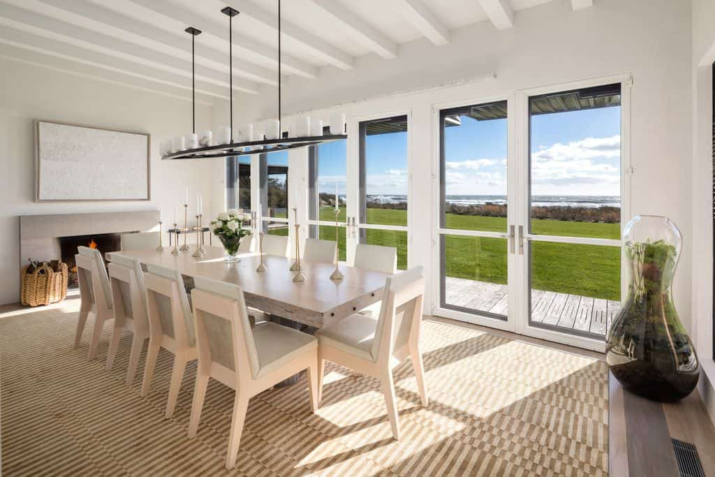 Beach-style dining room with white rectangular table and fireplace.