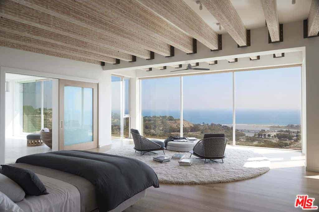 Exposed large wood beams add character in this contemporary primary bedroom with a panoramic window framing a breathtaking view. It is a spacious room filled with a comfy bed and a seating area over a round white rug. On its side is a sliding door that opens to the primary bathroom.