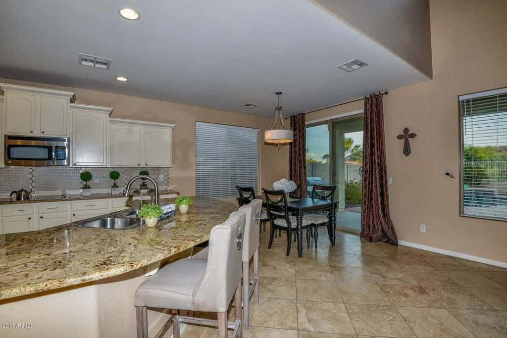 Contemporary beige dine-in-kitchen with peninsula breakfast bar and tile flooring.