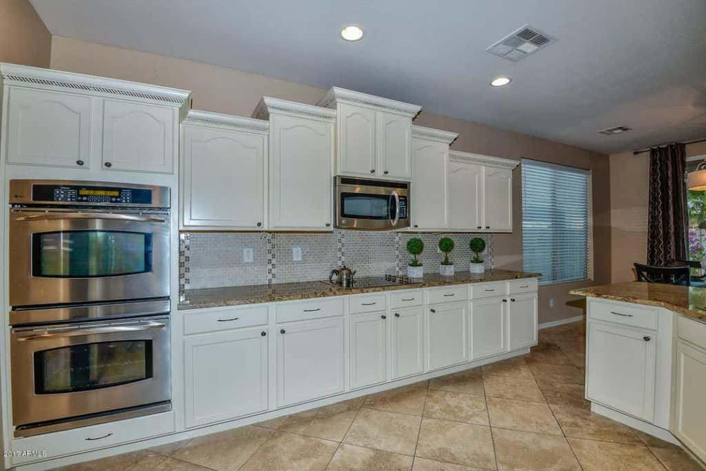 Contemporary kitchen with white recessed panel cabinetry, stainless steel appliances and tile flooring.
