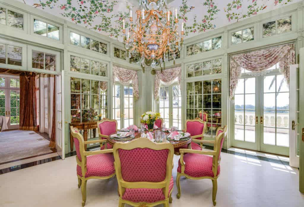 Country dining room with chandelier and red accent chairs.