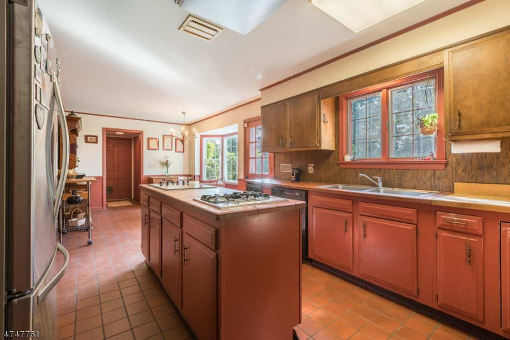 Farmhouse galley kitchen with yes island and tile flooring.