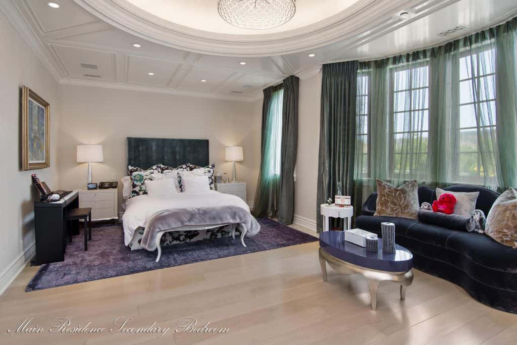 Mediterranean bedroom with tray ceiling and white interior. The room boasts a stunning tray ceiling and a stylish bed and rug.
