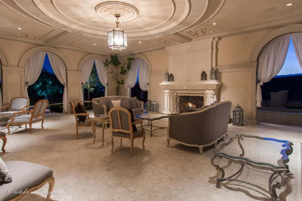 Large Mediterranean living room offering cozy seats and a fireplace along with glamorous windows and curtains.