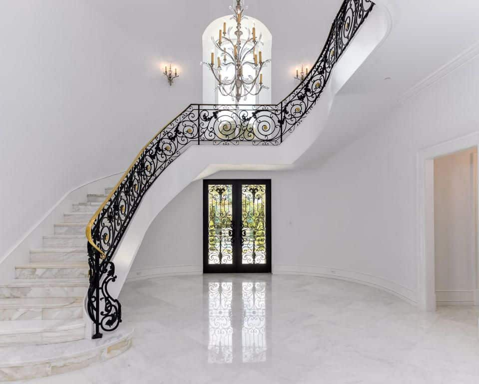 A home's entry with a white staircase with marble tiles floors and elegant-looking black railings lighted by a stunning chandelier.