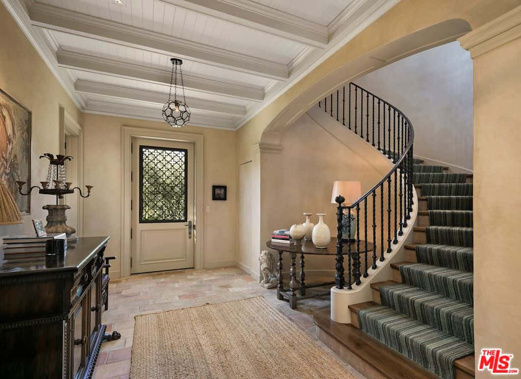 Industrial foyer features a black orb chandelier that hung from a white wood beam ceiling. It has a curved staircase with ornate iron spindles and wooden steps covered with a striped runner.