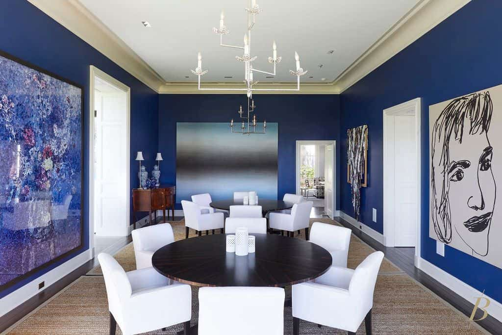Midcentury dining room with chandelier, white accent chairs, and round dining table.