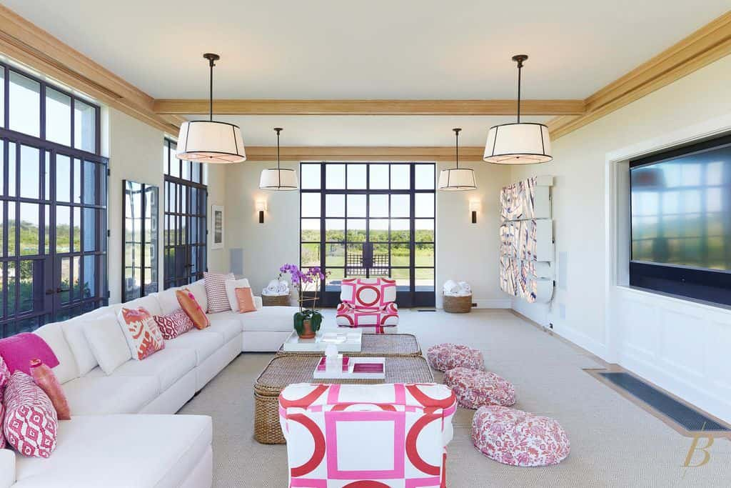 This living room features cute pink shade together with the white walls matching the sofa set lighted by pendant and wall lights.
