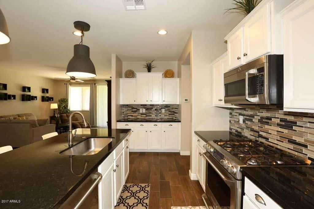 Small Modern White Kitchen With Multi Colored Tile Backsplash, Stainless  Steel Appliances And Hardwood
