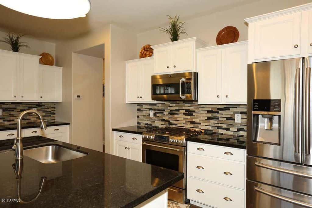 Small U Shaped Modern Kitchen With White Cabinetry, Multi Colored  Backsplash And Stainless Steel Appliances.Source: Zillow Digs