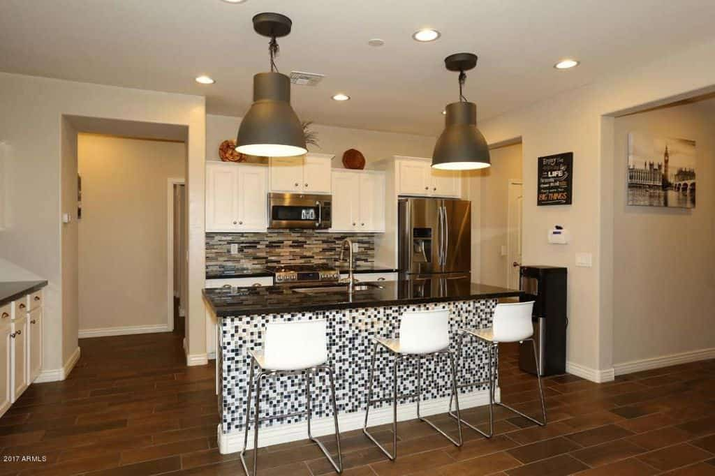 Small Modern Kitchen With White Cabinetry, Mosaic Backsplash And Stainless  Steel Appliances.