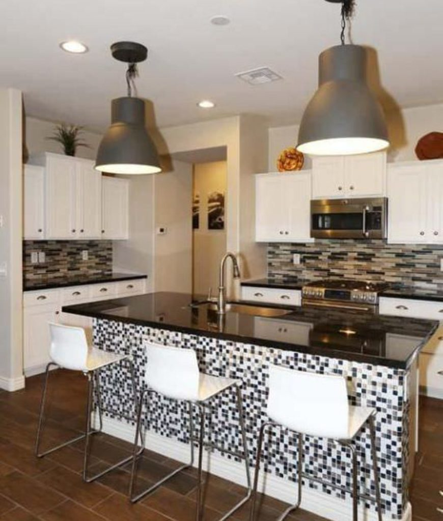 Small modern white kitchen with pendant lighting over island breakfast bar.