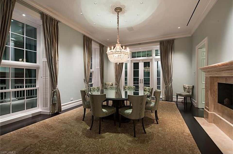 Traditinal dining room with white walls and chandelier.