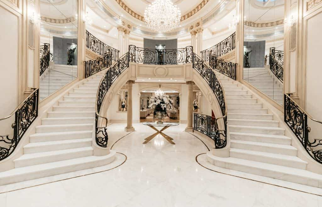 A luxurious grand foyer with a magnificent double staircase with white floors and black railings lighted by a glamorous chandelier.