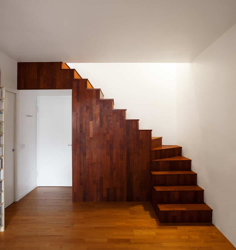 All wood staircase above entry door with no railing (space-saving staircase)