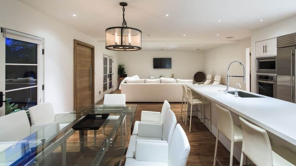 Just behind the living room is the dining set featuring a rectangle glass-top table with a candle light chandelier. Beside is the breakfast bar with white chairs and counter top.