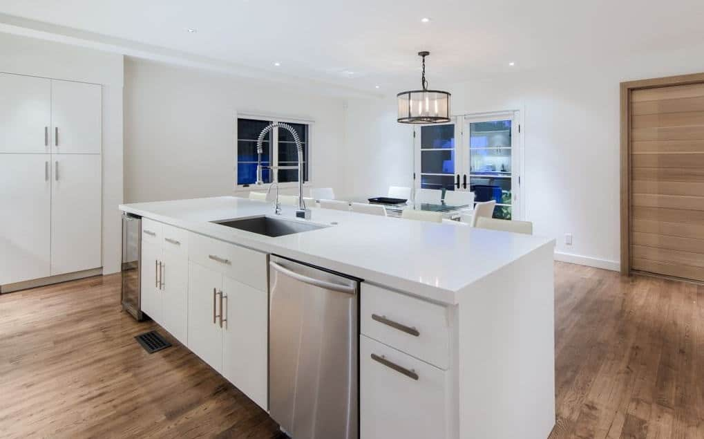 The simple kitchen boast the stainless steel appliances while the hardwood flooring matches the white theme.