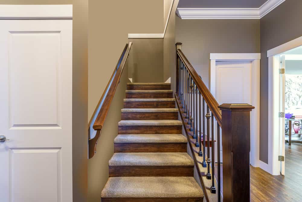 Staircase with carpet on tread only with exposed wood riser.