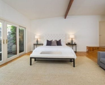 Another one of Anna's bedrooms featuring a wide rug on top of the hardwood flooring surrounded by the white walls and lighted by two lampshades.